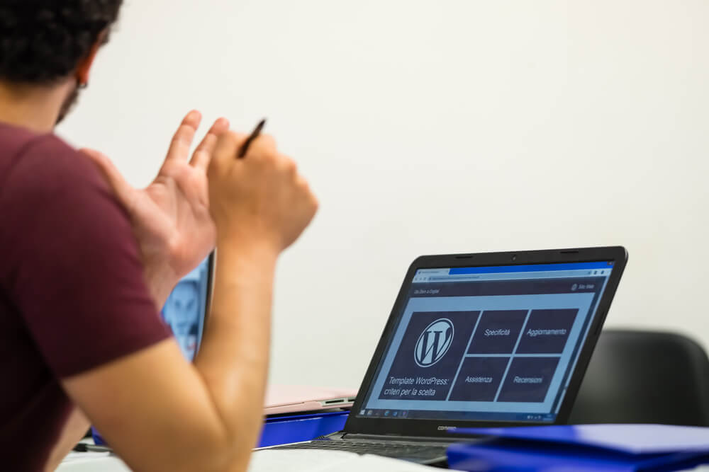 Young student with pen in hand and laptop resting on desk, visible the WordPress logo on the screen