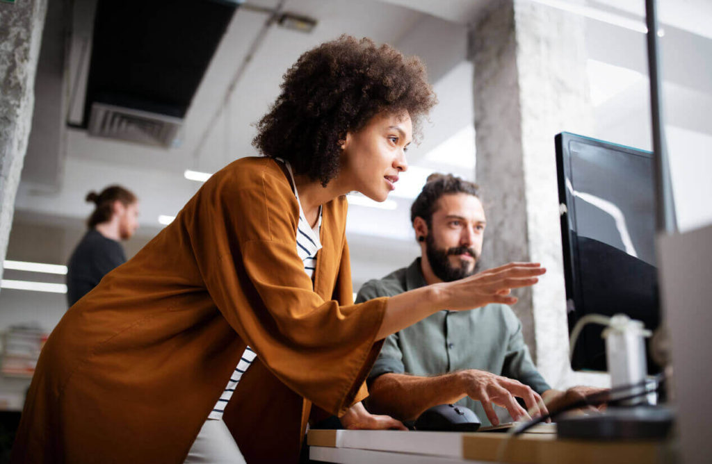 Young woman working with man on the computer in office space